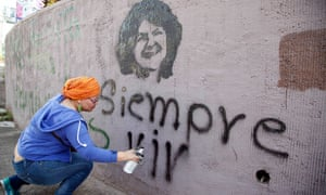 A woman spray-paints the phrase 'Always Alive' below a stencilled image of Berta Cáceres during the commemoration of international women's day in Tegucigalpa on 8 March.