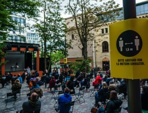 A sign reads 'Please keep a distance of 1.5 meters' during the presentation of 'Die Blechtrommel' (The Tin Drum) on an open-air stage in front of socially distanced spectators in the yard of the Berliner Ensemble theatre in Berlin, Germany.
