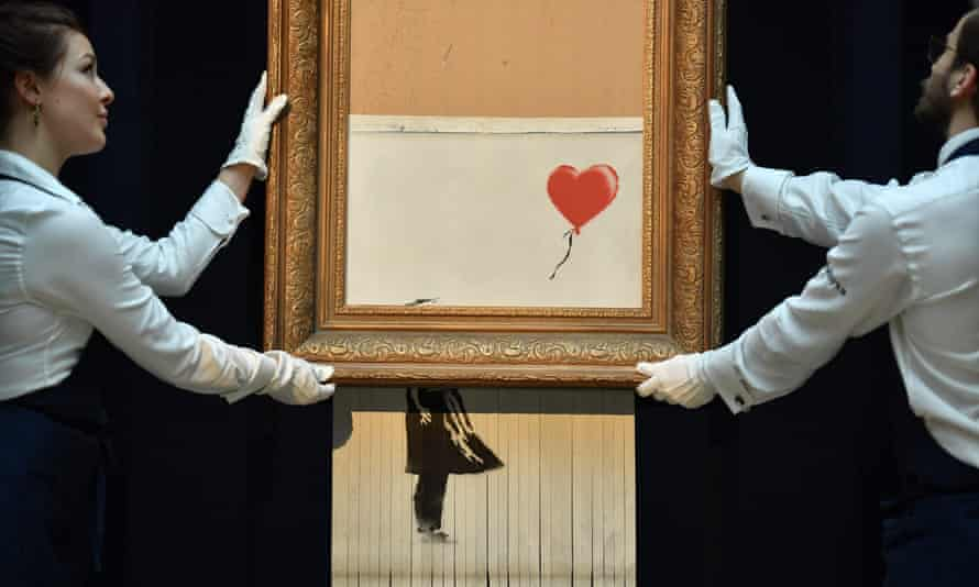 Sotheby's employees pose with Banksy's Love is in the Bin, which was created when the painting Girl With Balloon was passed through a shredder in London in October 2018