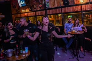 Medellín, Colombia. A woman sings as a band performs at a bar after Medellín left behind its strict quarantine and began to ease restrictive measures, mainly aimed at relaunching commerce