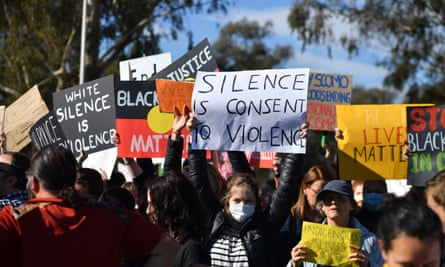 Black Lives Matter protesters hold placards as they gather outside Parliament House in Canberra, Australia, 5 June 2020.