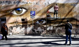 People walk past a mural by artist My Dog Sighs