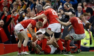 Josh Adams (No 11) is mobbed by his Wales teammates after his late try sealed victory.