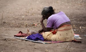 A Tamil woman sits on the ground in the Manik Farm refugee camp