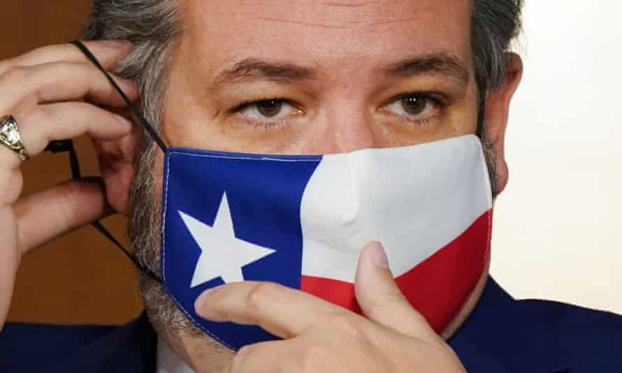Ted Cruz adjusts his mask.