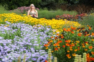Sophie Rochelle walk past beds of asterids in the Agius Evolution garden within Kew Gardens, London.