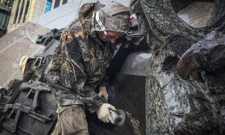 A man uses an angle grinder to remove part of the monument to Mikhail Kalashnikov allegedly featuring a German StG 44 rifle.