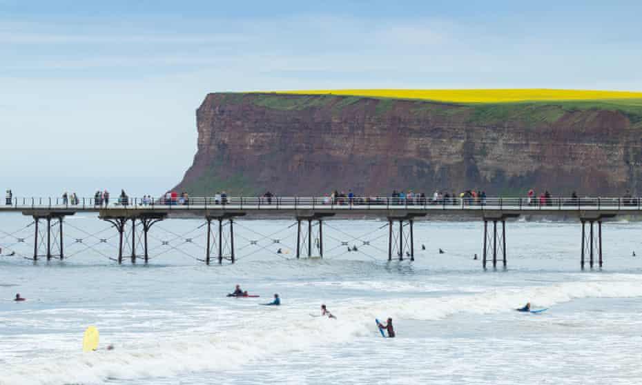 Surfers wait for a wave next to Saltburn's Victorian pier.