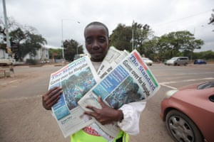 A man sells newspapers with headlines demanding Robert Mugabe's resignation