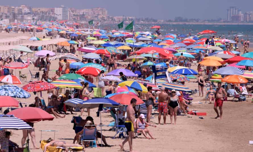 A beach thronged with people under multicoloured parasols