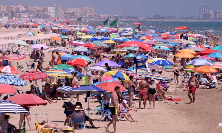 Une plage bondée de monde sous des parasols multicolores