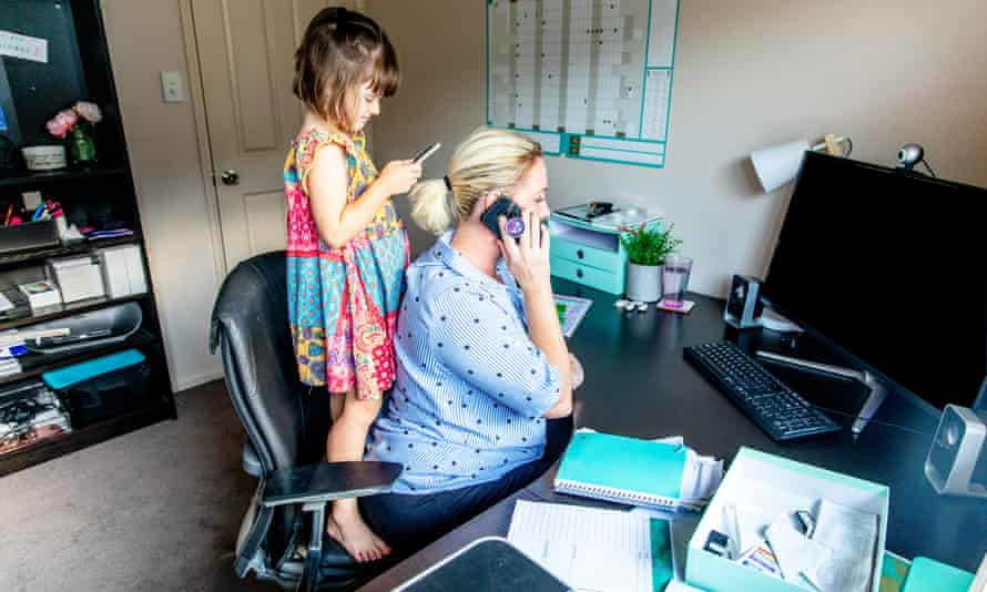 Middle Aged Woman working from home in office whilst also looking after her young daughter