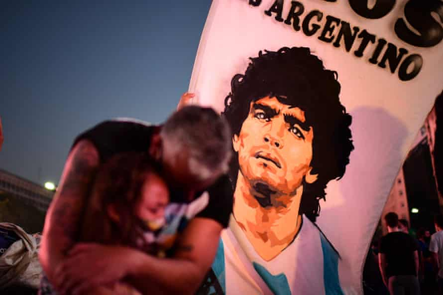 A father and his daughter pay homage to Diego Maradona on the day of his death in Buenos Aires, 25 November 2020.