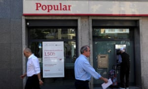 People walk past a Banco Popular branch in Madrid, Spain, yesterday.
