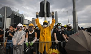 A protester wearing a yellow raincoat shouts and gestures at a barricade on Lung Wo road outside the government headquarters.