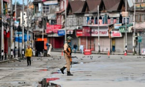 A member of the Indian security forces patrols a deserted road in Srinagar