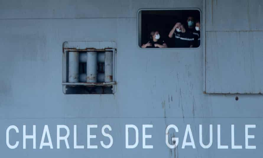French navy sailors wearing face masks seen through a porthole.