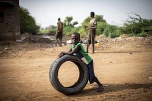 A boy plays with a tyre in Khartoum.