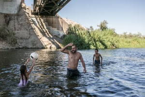 David Barraga plays ball with his daughter Dariana and his step-son Damien in the Colorado River in Gateway Park, Yuma, Arizona on 7 September 2019.