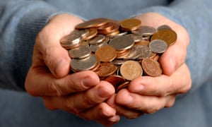 Two hands full of sterling coins