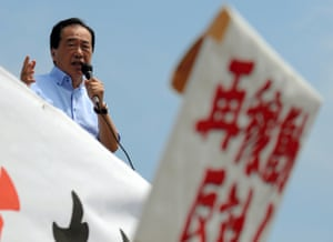 Former prime minister Naoto Kan speaks to protesters gathered at the main gate of the Sendai nuclear power plant.