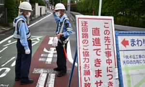 Security guards monitor traffic outside a construction site in Tokyo on 30 June 2020.