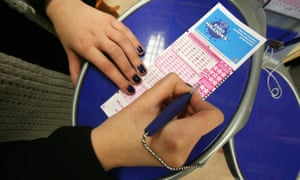 A woman filling in a EuroMillions lottery ticket in London