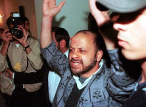 Iranian investigative journalist Akbar Ganji shouts at jailers as he arrives at Tehran's Revolutionary Court in November 2000.