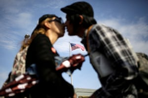 A flag of the US flutters behind a Mexican couple kissing before crossing into El Paso, Texas on the Paso del Norte bridge.