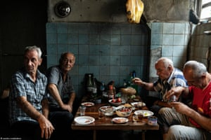 Italy 20. Politics - Sandro Maddalena - Old friends - Tskaltubo - Refugees from the Abkhazian - Georgian conflict gather in the basement of an abandoned sanatorium to share their food. Almost thirty years after the conflict, Abkhazian refugees are still living in abandoned buildings in conditions of poverty.