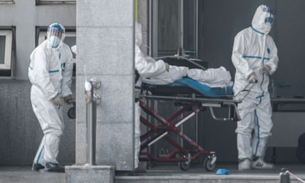 Staff carry a patient into the Jinyintan hospital, where patients infected by a mysterious Sars-like virus are being treated, in Wuhan