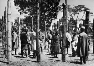 Soldiers guard suspected Mau Mau fighters in Kenya in 1952, during the Mau Mau uprising against British colonial rule.