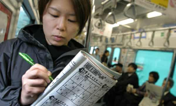A commuter in Japan completing sudoku puzzles on a train