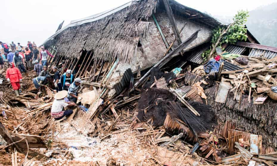 Rescue workers search for victims near a collapsed house following landslides at Cisolok district in Sukabumi, West Java