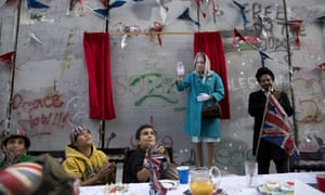 The party, held beneath the looming concrete separation wall, featured scorched union flags and bunting.