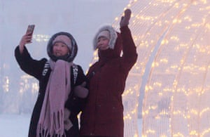 Women brave the freezing temperatures to take selfies in Lenin Square
