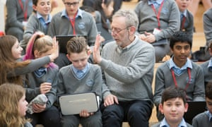 Michael Rosen surrounded by pupils