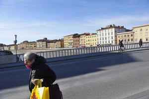 A woman walks on the Ponte di Mezzo by the river Arno in a semi-deserted town on March 10, 2020 in Pisa, Italy. T