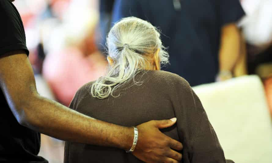 An elderly Sikh woman is helped to her chair in a care home in Bradford.