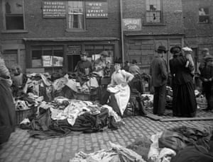 A secondhand clothes seller at Newcastle cloth market reads as customers inspect her goods. A set of original glass negatives showing street scenes of 19th century Newcastle has been found by Aaron Guy, who works at the city's Mining Institute.
