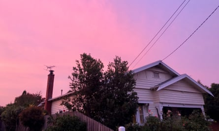An old weatherboard house against a purple and pink sky