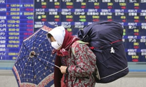 Elderly woman walks by an electronic stock board of a securities firm in Tokyo