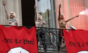 Topless Femen activists perform the Nazi salute as they demonstrate on a balcony against France's far-right Front National.