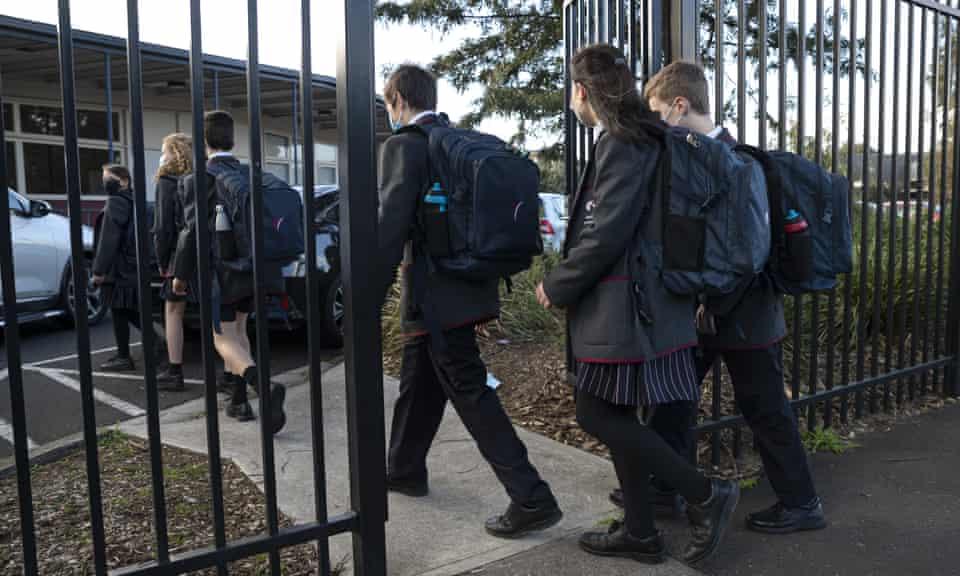 Children in uniform walking through school gates