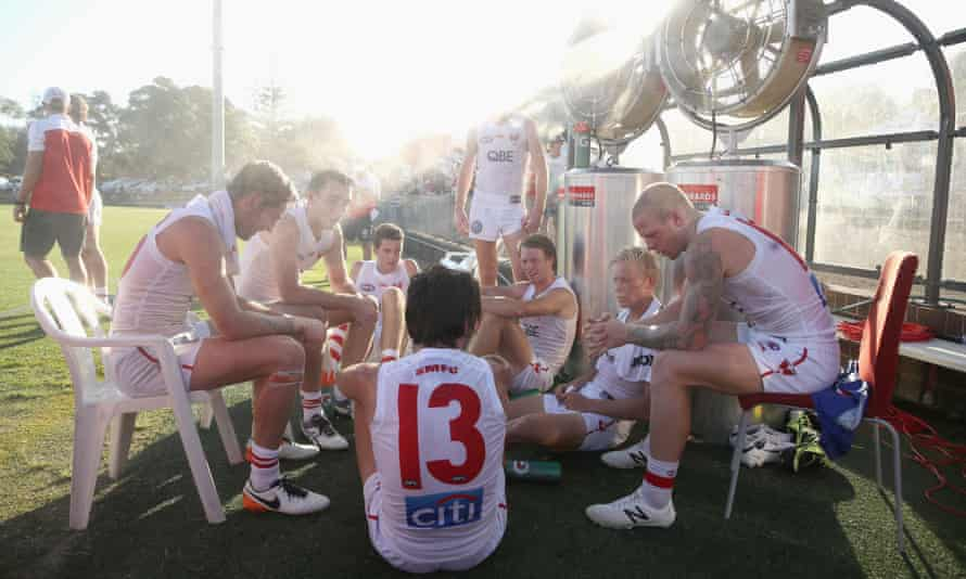 Players from the Swans White team cool down in front of the misting fans during the halftime break in their match on Friday.