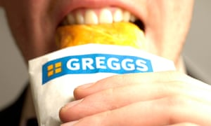 A man enjoying his recently purchased Greggs sausage roll.
