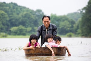 Jiangxi province, China. A man wades through flood waters with his children in Duchang county