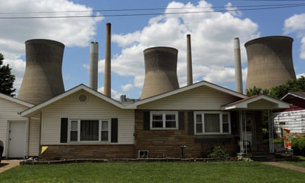 A coal-fired power plant is seen behind a home in Poca, West Virginia.