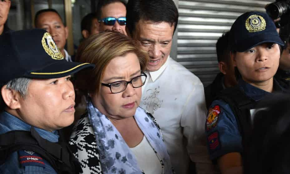 Senator Leila De Lima is escorted by police officers after her arrest.