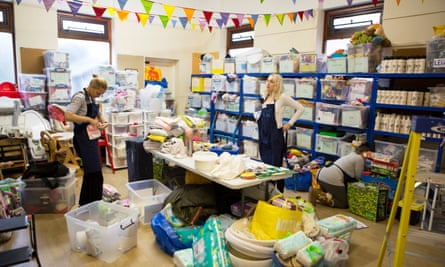 Little Village volunteers sort donated baby clothes and equipment